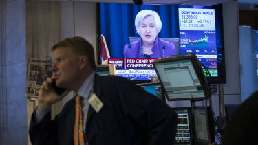 Janet Yellen on TV while traders work