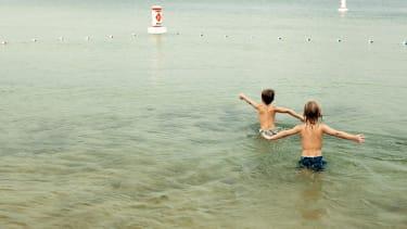Boys swimming in a lake.