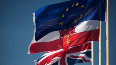 A Union Jack flag, Gibraltar's flag, and the EU flag