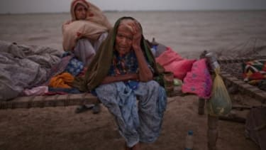 Pakistani women, whose families were displaced by floods, sit on a makeshift bed, as they take shelter on higher ground in Pakistan.