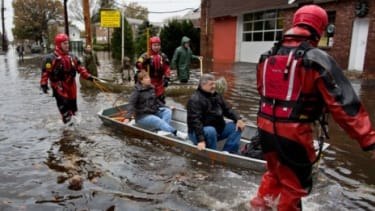 Rescuers bring flood victims out by boat in Little Ferry, N.J., on Oct. 30