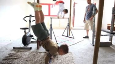 Brothers Giuliano (right) and Claudiu Stroe (left) can be seen in their gym doing vertical push-ups as part of their intense training regimen.