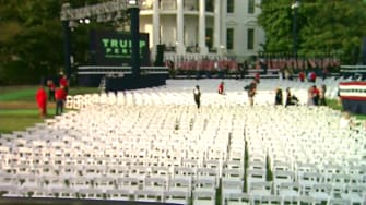 White House lawn with hundreds of chairs pushed side by side.