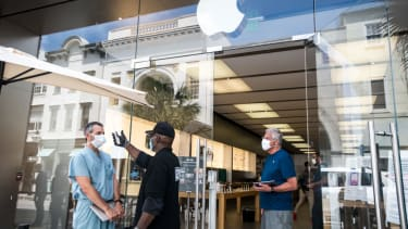 A security guard takes the temperature of a customer outside the Apple Store on May 13, 2020 in Charleston, South Carolina