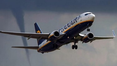 Photo captures passenger plane taking off just as a tornado prepares to touch down
