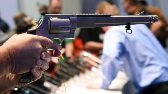 A shooting convention attendee holds a handgun