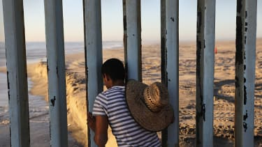 A person looks from the Mexico side of the border at the U.S.