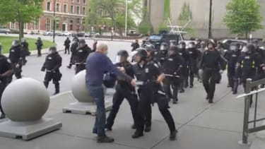 Police shove 75-year-old protester.