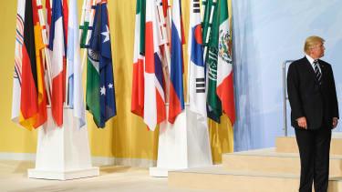 President Trump standing beside international flags.