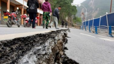 People walk next to a crack in the road after Saturday's earthquake in Baoxing county, Sichuan province, April 21.