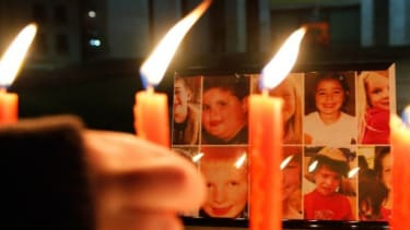A boy pays his respects to the victims of the Sandy Hook Elementary shootings during a candlelight vigil in Tirana, Albania.