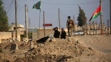 Syrian civilians wait at a checkpoint.