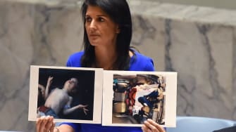 Nikki Haley holds up photos of victims of the Syria chemical attack.