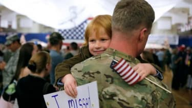 A child hugs his father who returned from Afghanistan on Nov. 4, 2012, after a nine-month deployment.