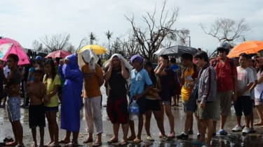 Affected residents wait in line for relief goods in Tacloban City, Philippines. Around 10,000 people are feared dead in Typhoon Haiyan, the strongest to hit the Philippines this year.
