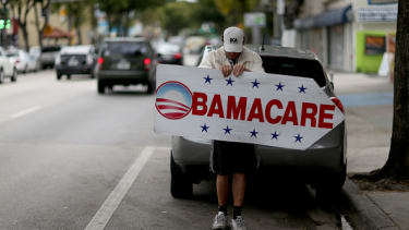 Woman holds an ObamaCare sign.