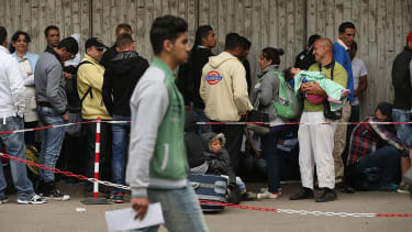 Refugees in Germany wait outside the Central Registration Office for Asylum Seekers