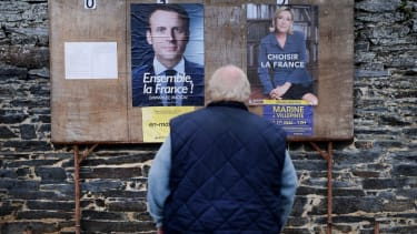 A man stands in front of French presidential campaign posters