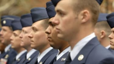 A predominately white and male Military line up for a Veteran's Day Parade.