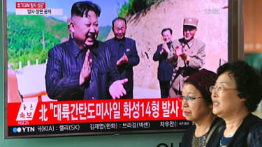 Women walk by news coverage of the North Korean missile launch.