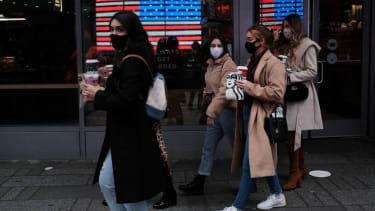 People wearing masks walk through Times Square.