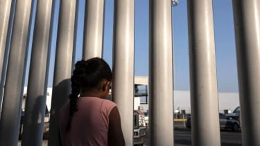 Girl looking through fence at U.S. Mexico border.