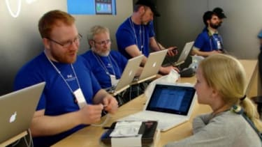 """Apple employees help a young customer in Portland, Ore.: To become a """"Genius,"""" employees must go through a mandatory 14-day course."""