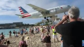 A plane lands at Princess Juliana International Airport.