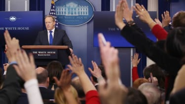 Sean Spicer confronts a room of reporters with raised hands.
