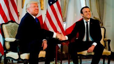 Trump and Emmanuel Macron shake hands, fiercly