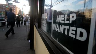A help wanted sign hangs in a window