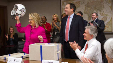 Hillary Clinton holds a football helmet gifted by Deputy Secretary Tom Nides in 2013.