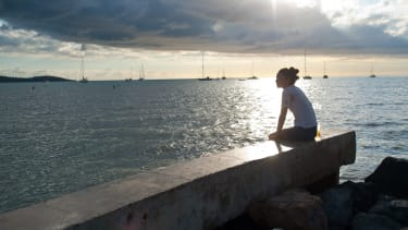 A woman sitting by the ocean.