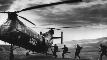 American troops run for a helicopter after a successful attack behind enemy lines during a training session in 1962.