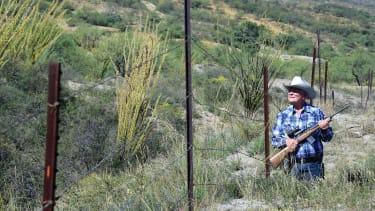 Jim Chilton walks beside a border fence on his ranch in Arivaca, Arizona.