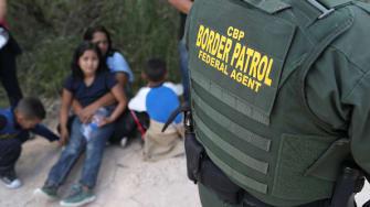 A border patrol agent takes asylum seekers into custody.