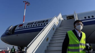 A member of staff, wearing a facemask for protective measures, disembarks from an Air China airbus carrying 500.000 protective masks at the Athens international airport, on March 21, 2020, as
