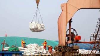Chinese workers unload bags of soybean meal