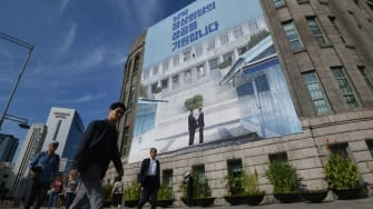 Pedestrians walk past a giant banner showing a picture of the summit handshake between South Korean President Moon Jae-in and North Korean leader Kim Jong Un.