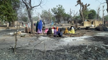 Women and children sit amid burned homes after a Boko Haram attack in Nigeria.