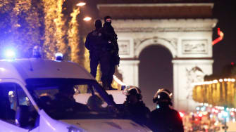 Masked gunman guard the Champs Elysees Avenue after a gunman opened fire.