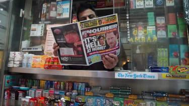 "A man reads the ""National Enquirer."""