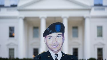 A poster of Chelsea Manning's face in front of the White House