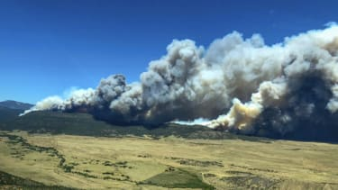 Plumes of smoke from a wildfire near Cimarron, N.M., rise in the background Friday, June 1, 2018.