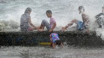 People on a beach in the Philippines during Typhoon Noul.