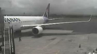 Airport surveillance camera captures stowaway teen stumbling around plane after landing