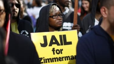 A woman holds a sign calling for the arrest of George Zimmerman during a protest in Los Angeles: More details about Trayvon Martin's shooter are emerging.