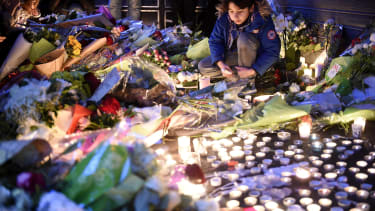 A child looks at tributes left at the site of one of the terrorist attacks on Paris in 2015.