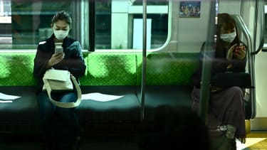 Women look at their phones on the train in Tokyo.