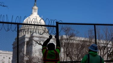 Workers install barbed wire on security fencing surrounding the U.S. Capitol